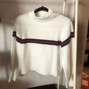 White turtle neck sweater with 3 stripes.